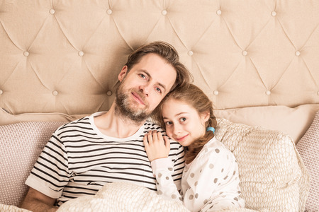 Smiling caucasian father and daughter in pyjamas hugging in a bed. Morning in a bedroom - happy family time.