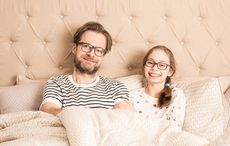 Portrait of happy smiling caucasian father and daughter wearing pyjamas and glasses in a bed. Morning in a bedroom - happy family time.