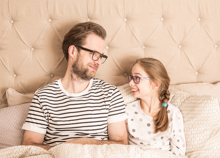 Happy smiling caucasian father and daughter looking at each other while wearing pyjamas and glasses in a bed. Morning in a bedroom - happy family time. Standard-Bild