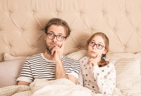 Thoughtful or bored caucasian father and daughter wearing pyjamas and glasses in a bed. Morning in a bedroom - family time. Standard-Bild