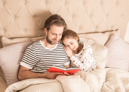 Caucasian father and daughter in pyjamas reading a book in a bed. Morning in a bedroom - happy family time.