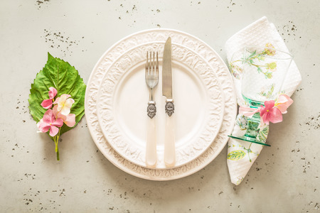 Easter, spring or summer table setting design captured from above (top view, flat lay). Ornamental white plates, glass, cutlery and pink flowers. Grey stone background.