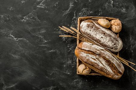 ベーカリー - 黒い黒い黒板の背景にパンとパンの金素朴な皮のローブ。上から撮影された静物(上図、フラットレイ)。空きコピー (テキスト) 領域を