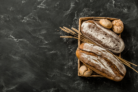 Bakery - gold rustic crusty loaves of bread and buns on black chalkboard background. Still life captured from above (top view, flat lay). Layout with free copy (text) space. 스톡 콘텐츠