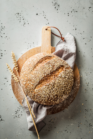 Gold round loaf of rustic bread and ears of wheat on wooden board captured from above (top view, flat lay). Grey stone background. Layout with free copy (text) space.