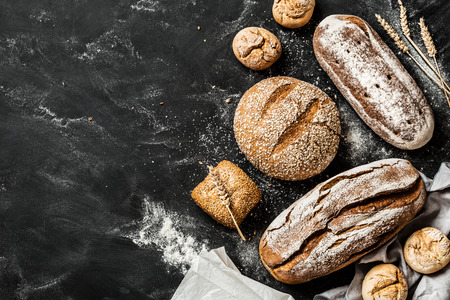 Bakery - gold rustic crusty loaves of bread and buns on black chalkboard background. Still life captured from above (top view, flat lay). Layout with free copy (text) space. Stockfoto