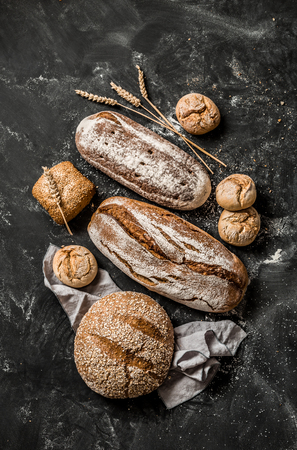 Bakery - gold rustic crusty loaves of bread and buns on black chalkboard background. Still life captured from above (top view, flat lay). Standard-Bild