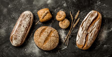 ベーカリー - 黒い黒い黒板の背景にパンとパンの金素朴な皮のローブ。上から撮影された静物(トップビュー、フラットレイ)、バナーレイアウト。 写真素材