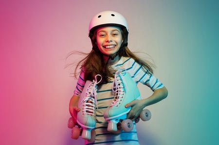 Feliz sonriente joven niña caucásica en casco de seguridad con patines pastel - concepto de hobby, deportes y estilo de vida activo. Fondo colorido, diseño con espacio de texto libre (copia).
