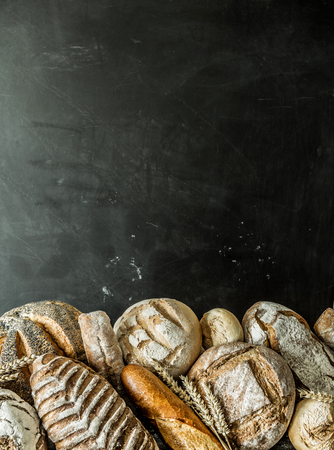 Bakery stall - gold rustic crusty loaves of bread and buns exposed on black chalkboard background. Poster layout with free copy (text) space. Stock fotó
