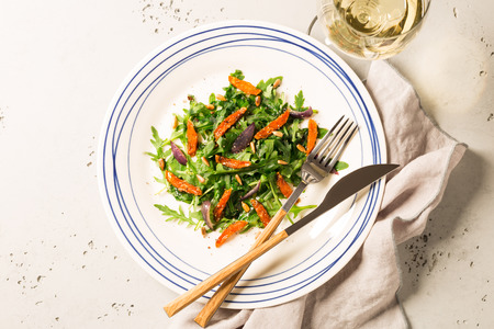 Salad with arugula (rucola), caramelised carrot, onion and sunflower seeds. Plate captured from above (top view, flat lay). Grey stone background. Stock Photo