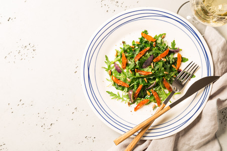 Salad with arugula (rucola), caramelised carrot, onion and sunflower seeds. Plate captured from above (top view, flat lay). Grey stone background. Layout with free text space. Reklamní fotografie