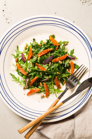 Salad with arugula (rucola), caramelised carrot, onion and sunflower seeds - close up. Plate captured from above (top view, flat lay). Grey stone background.