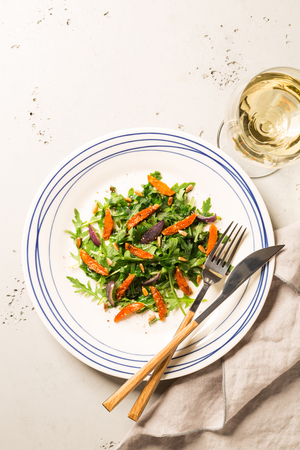 Salad with arugula (rucola), caramelised carrot, onion and sunflower seeds. Plate captured from above (top view, flat lay). Grey stone background. Layout with free text space. Stock Photo