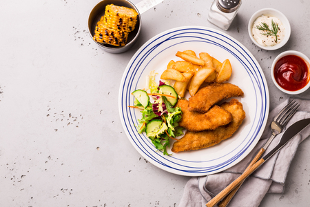 Lunch or dinner - fried chicken strips, french fries, roasted corn, salad and dips. Plate captured from above (top view, flat lay). Grey stone background with free text space. Reklamní fotografie