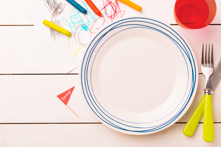 Tischdekoration für Kinder. Leerer Teller auf weiß beplanktem Holztisch mit bunten Dekorationen - von oben aufgenommen (Draufsicht, flach). Layout mit freiem Text (Kopie) Platz.