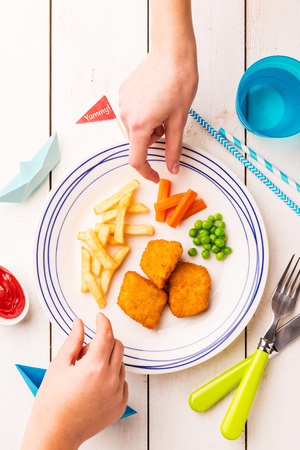 Small kid's meal - fish, chips, carrot and green peas. Colorful dinner on white wooden table with children's hands around. Plate captured from above (top view, flat lay). Standard-Bild - 123610244