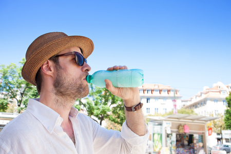 Forty years old caucasian tourist man drinking water out of bottle outdoor in a hot city. Summer holiday traveling.