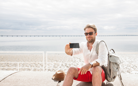 Happy smiling forty years old caucasian tourist man takes a photo of himself (selfie) with mobile phone (smartphone). Beach and sea as background - summer holiday traveling.