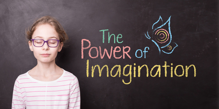 Blond child girl (pupil) with eyes closed at the school chalkboard (blackboard) with The Power of Imagination sign. Education - kid dreaming or imaging something in the classroom. 스톡 콘텐츠