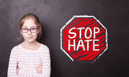 Unhappy or angry blond child girl at the school chalkboard (blackboard) with STOP HATE sign. Education - hating, bullying and aggression problem.