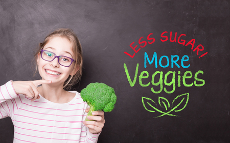 Happy smiling blond child girl holding broccoli. School chalkboard with Less Sugar, More Veggies sign as background. Healthy diet, nutrition and eating habits - motivational poster design. 스톡 콘텐츠