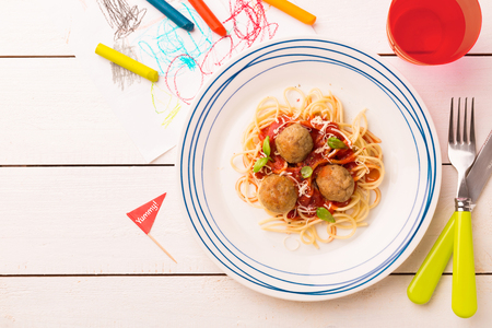 Small kid's meal - spaghetti and meatballs. Colorful italian dinner on white wooden table. Plate captured from above (top view, flat lay). Layout with free copy (text) space. Standard-Bild