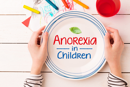 Plate with a leaf and Anorexia in Children sign in kids hands. Eating disorders - concept captured from above (top view, flat lay). Crayons and childs drawing around. Stock Photo