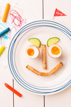 Kids breakfast - funny face made of eggs, toasts and cucumber. Plate captured from above (top view, flat lay) on white wooden table. 스톡 콘텐츠