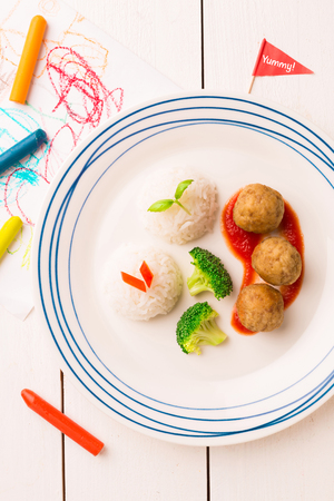 Small kids meal - meatballs, rice and broccoli. Colorful dinner on white wooden table. Plate captured from above (top view, flat lay). 스톡 콘텐츠