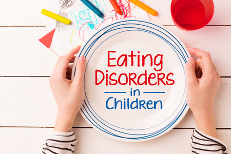 Plate with Eating Disorders in Children sign in kids hands. Anorexia and bulimia problem - concept captured from above (top view, flat lay). Crayons and childs drawing around. 스톡 콘텐츠