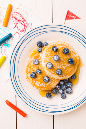 Kids breakfast meal - pancakes, blueberries and maple syrup. Plate captured from above (top view, flat lay) on white wooden table. 스톡 콘텐츠