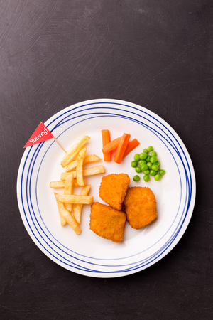 Small kids meal - chicken nuggets, chips, carrot and green peas. Colorful dinner on black chalkboard background. Plate captured from above (top view, flat lay). Layout with free copy (text) space.