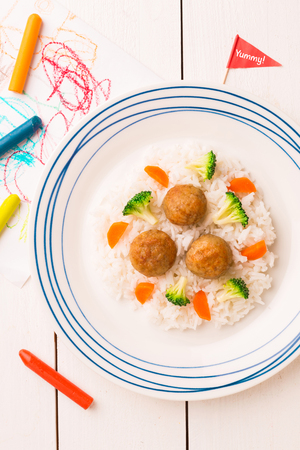 Small kids meal - meatballs, rice, broccoli and carrot. Colorful dinner on white wooden table. Plate captured from above (top view, flat lay).