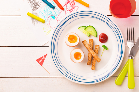 Kids breakfast - eggs, toasts, cucumber and ketchup. Plate captured from above (top view, flat lay) on white wooden table. Layout with free copy (text) space. Reklamní fotografie