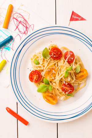 Small kids meal - spaghetti with cherry tomatoes and basil. Colorful italian dinner on white wooden table. Plate captured from above (top view, flat lay).