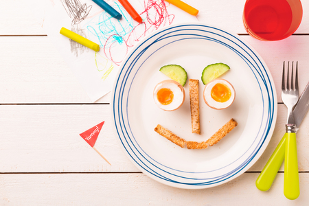 Kids breakfast - funny face made of eggs, toasts and cucumber. Plate captured from above (top view, flat lay) on white wooden table. Layout with free copy (text) space. 스톡 콘텐츠