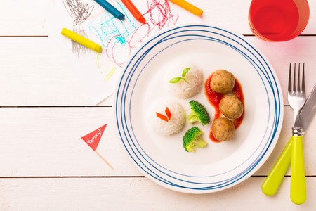 Small kids meal - meatballs, rice and broccoli. Colorful dinner on white wooden table. Plate captured from above (top view, flat lay). Layout with free copy (text) space.