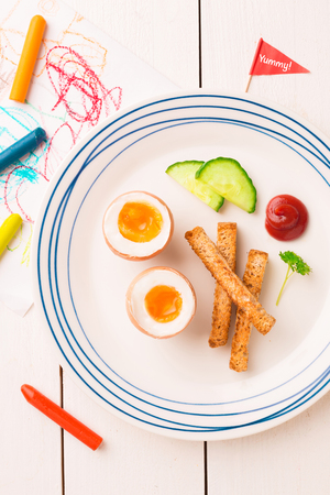Kids breakfast - eggs, toasts, cucumber and ketchup. Plate captured from above (top view, flat lay) on white wooden table.