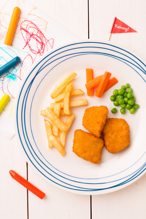 Small kids meal - chicken nuggets, french fries, carrot and green peas. Colorful dinner on white wooden table. Plate captured from above (top view, flat lay).