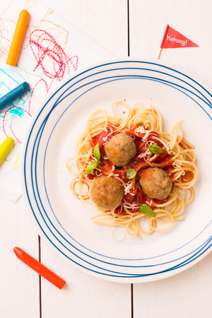 Small kids meal - spaghetti and meatballs. Colorful italian dinner on white wooden table. Plate captured from above (top view, flat lay).