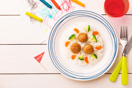 Small kids meal - meatballs, rice, broccoli and carrot. Colorful dinner on white wooden table. Plate captured from above (top view, flat lay). Layout with free copy (text) space.