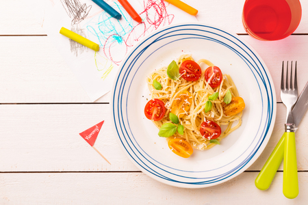 Small kids meal - spaghetti with cherry tomatoes and basil. Colorful italian dinner on white wooden table. Plate captured from above (top view, flat lay). Layout with free copy (text) space.