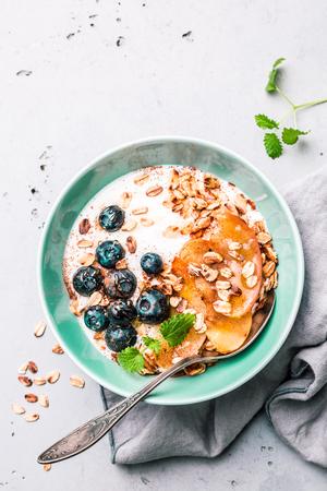 Gesundes Frühstück oder Dessert. Joghurt mit Haferflocken, Blaubeeren, Äpfeln und Honig in pastellblauer Schüssel auf grauem Steinhintergrund. Von oben aufgenommen (Draufsicht, flache Lage). Freier Kopienraum (Text). Standard-Bild