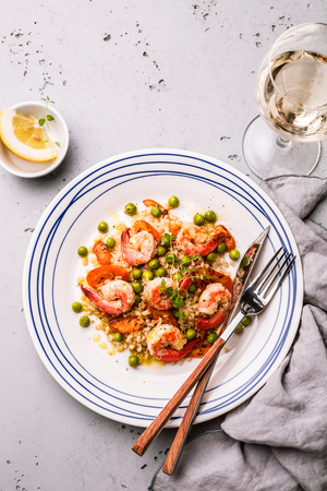 Colorful dinner (lunch) - prawns (shrimps), bulgur, carrot and green peas on white plate. Meal captured from above (top view, flat lay) on the grey stone background. Free copy (text) space.