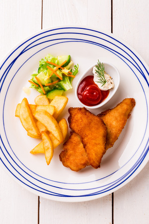 Kids meal  - fried chicken strips, french fries, salad and ketchup. Colorful dinner on white wooden table. Plate captured from above (top view, flat lay). Reklamní fotografie