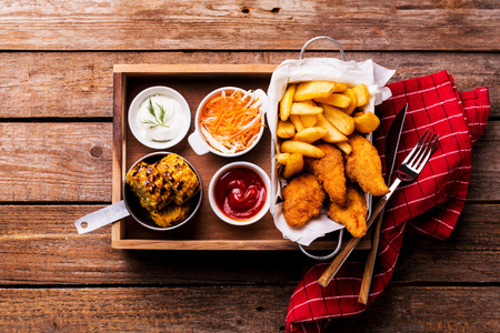 Country or rustic restaurant dinner - fried chicken strips, french fries, roasted corn, salad and dips. Wooden table captured from above (top view, flat lay).