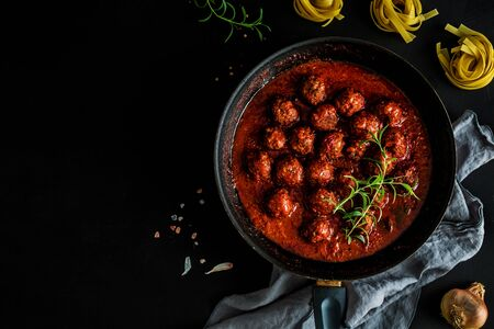 Meatballs in tomato sauce with rosemary on the pan. Dish captured from above (top view, flat lay) on black background. Free copy (text) space. Dark moody composition.