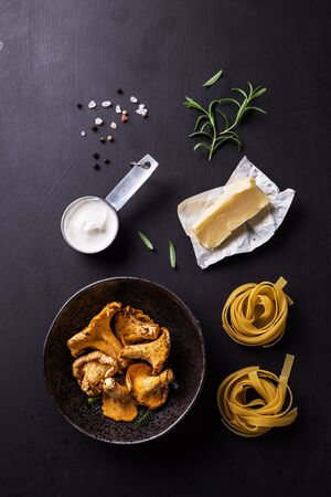 Cooking - tagliatelle with chanterelle mushrooms, cream, butter and rosemary. Recipe ingredients on black background captured from above (top view, flat lay). Free copy (text) space.