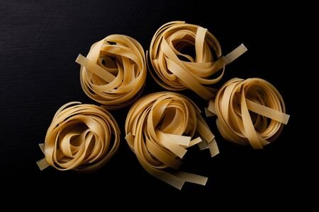Raw tagliatelle pasta on black background close up. Captured from above (top view, flat lay). Dark moody composition.